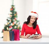 christmas, x-mas, online shopping concept - smiling woman in santa helper hat with shopping bags and