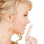 business, communication concept - picture of mysterious woman with finger on her lips