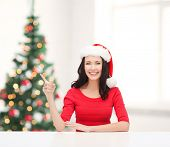 christmas, x-mas, winter, happiness concept - smiling woman in santa helper hat pointing to somethin