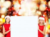 christmas, x-mas, people, advertisement, sale concept - happy women in santa helper hats with blank