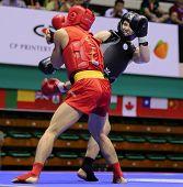 KUALA LUMPUR - NOV 03: Malaysia's Tan Jia Guan in red blocks Sweden's Johan Lindqvist's kicks in the