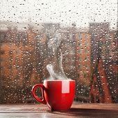 stock photo of cold-weather  - Steaming coffee cup on a rainy day window background - JPG