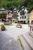 image of public housing  - Public water fountain with colorful houses village marketplace square in Hallstatt Austria - JPG