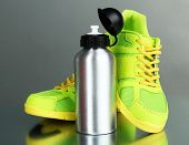 stock photo of canteen  - Sports bottle and sneakers on grey background - JPG