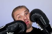 Man getting punched by a pair of boxing gloves.