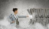 stock photo of karate  - Image of businesswoman breaking bricks with hand - JPG
