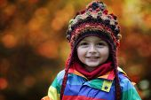 image of beanie hat  - Little boy in Autumn park wearing a warm beanie hat - JPG
