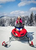 Couple driving snowmobile in winter mountain