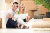 stock photo of family planning  - Young happy couple moving into their new home with plan  - JPG