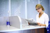 A serious girl with glasses reading a newspaper at the table