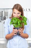 Young woman smelling on fresh basil