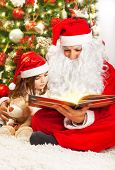 Image of little girl reading book with Santa Clause, small child with grandpa wearing red festive costume sitting on the floor near decorated Christmas tree, read fairytale, happy childhood concept