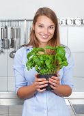 Young woman with fresh herbs in her kitchen