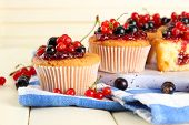 Tasty muffins with berries on white wooden table