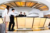 stock photo of receptionist  - Asian Chinese woman and man arriving at front desk or reception of luxury hotel in business clothes with trolley - JPG