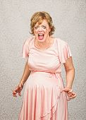 stock photo of outrageous  - Desperate pregnant person in pink dress on gray background - JPG