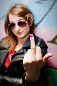image of fuck  - Stylish fashionable girl showing fuck off middle finger gesture against colorful graffiti wall - JPG