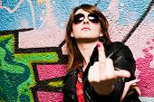 stock photo of fuck  - Stylish fashionable girl showing fuck off middle finger gesture against colorful graffiti wall - JPG