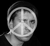 Serious young man with peace symbol over his face; concept of peace awareness and anti-war movement