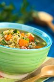 picture of scallion  - Vegetarian quinoa soup with carrot potato leek and tomato sprinkled with parsley and scallion in colorful bowl 