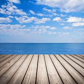 Empty Wooden Pier With Sea And Cloudy Sky On Background