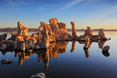 Orange sunset on Mono Lake. Outliers - bizarre calcareous tufa formation  reflected in the smooth wa