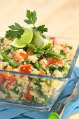 foto of quinoa  - Vegetarian quinoa dish with green asparagus and red bell pepper garnished with lime wedges and parsley leaf served in glass bowl (Selective Focus Focus on the asparagus head on the dish)