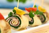 stock photo of crepes  - Crepe rolls as finger food filled with spinach and ham garnished with cherry tomato and watercress 