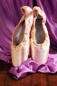 Ballet pointe shoes on wooden floor on fabric background