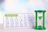 Hourglass and calendar on bright background