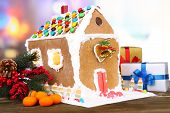 Beautiful gingerbread house with Christmas decor on wooden table