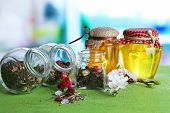Assortment of herbs and tea in glass jars on wooden table, on bright background