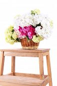 Wicker basket with flowers on small wooden ladder, isolated on white
