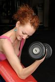 Young slim red haired girl doing biceps workout with dumbbell