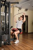 Handsome young man doing B lats pull-down workout in gym