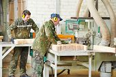 Workers of woodworking manufacture operating on machine