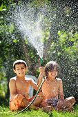 foto of fountain grass  - Happy kids playing and splashing with water sprinkler on summer grass yard - JPG