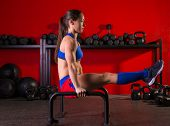 Parallettes woman parallel bars workout exercise at red gym