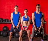 foto of kettlebell  - Kettlebell swing workout training group at gym with red wall - JPG