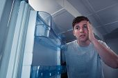 stock photo of refrigerator  - Portrait of a hungry man looking for food in refrigerator - JPG
