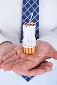 Businessman Holding Cigarettes Tied With Rope And Wick