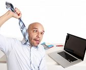 pic of strangled  - bald south american businessman choking himself with his own tie while being over worked and stressed on this laptop on a white background - JPG