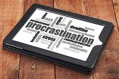procrastination word cloud on a digital tablet against red barn wood