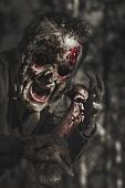 stock photo of spooky  - Spooky horror photograph of an evil male zombie with rotten face shouting out in bloody terror at dark haunted forest - JPG
