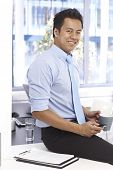Young Asian businessman smiling as sitting on top of desk, holding mobilephone and tea mug.