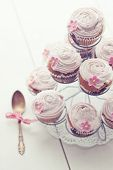 Pink cupcakes on cupcake stand on wooden background