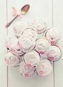 Pink cupcakes on cupcake stand on wooden background, top view