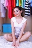 Beautiful young woman sitting on floor near wardrobe in room