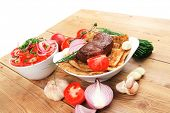 meat food : roasted fillet mignon on bread in white bowl garnished with tomatoes salad on wooden tab