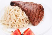 italian food : pasta with tomato on basil and roasted sirloin beef  steak on plate isolated over whi